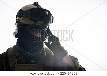 Portrait of calm defender speaking by portable radio set. Army and communication concept. Isolated and copy space