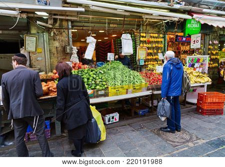 JERUSALEM, ISRAEL - DECEMBER 29, 2016: Shoppers at  Mahane Yehuda market in Jerusalem.  More than 250 traders on market sell fresh fruits and vegetables, baked products, fish, meat and others