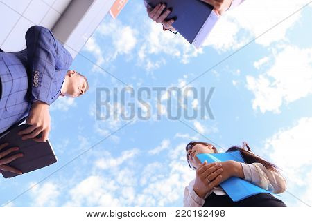 Two attractive successful woman and beautiful modern man, successful young office workers, businessmen, students communicate, make deal, shake hands, discuss working moments, versed in reports, kept in hands documents and view them