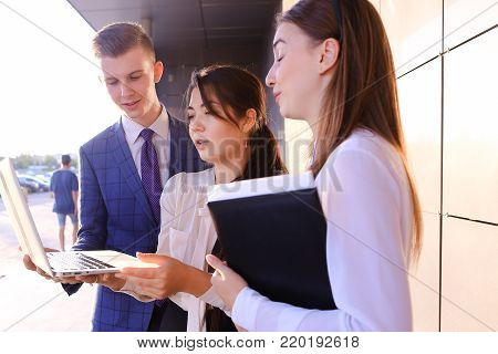 Modern young man and two attractive smart young women, business people, students communicate, holding laptop and study work plan, familiarize with presentation, teach each other new programs, solve important problems and workloads holding folder