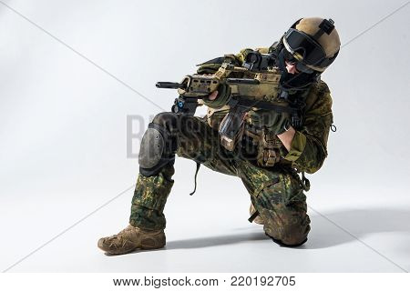 Portrait of serious defender looking at sniper scope of modern weapon. Military concept