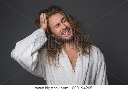 Waist up portrait of bushy guy holding one hand on head expressing negative emotions. Isolated on grey background