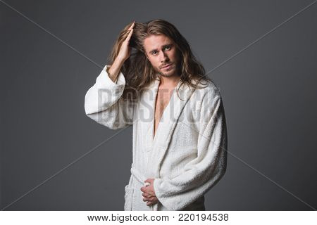 Waist up portrait of careless man in white bathrobe touching his locks. He is looking at camera with serenity. Isolated on grey background