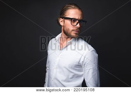 Waist up of stylish guy n glasses. He is looking carefree. Isolated on black background. Copy space in left side