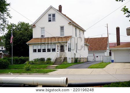 JOLIET, ILLINOIS / UNITED STATES - JULY 18, 2017: A three story white single family home, with a detached garage, in Joliet's Historic Cathedral Area.