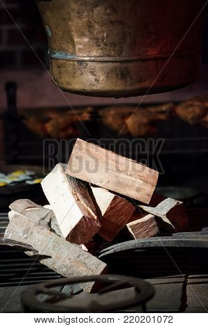 Closeup of old hearth bonfire with pile of fire wood and pot. Indoor.