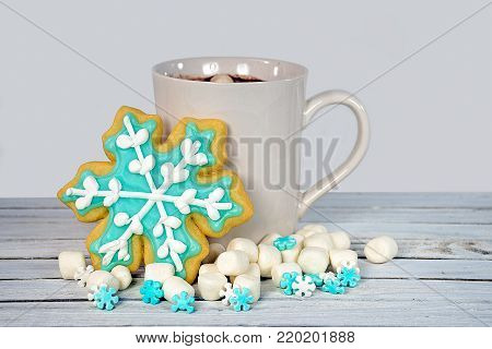 hot chocolate drink with snowflake sugar cookie and marshmallows on rustic whitewashed wood