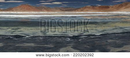 Blue transparent smooth surface of the mountain lake, coastal sand spit, in the background of the pink mountain range, the Himalayas, Tibet, photo panorama.