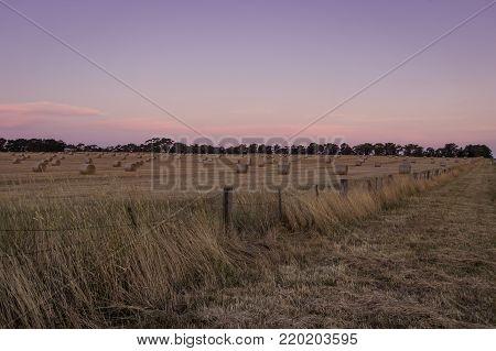 fenceline in rural Australia with hay bales in field