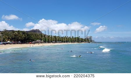 Honolulu - July 3, 2016: People ride waves in the water at Queens Beach in Waikiki with Diamondhead in the distance.