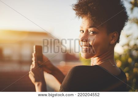 Close-up portrait of dazzling African American female with curly hair, partly turned to the camera while staying on the roof and taking pictures on mobile cell phone of cityscape on sunny summer day