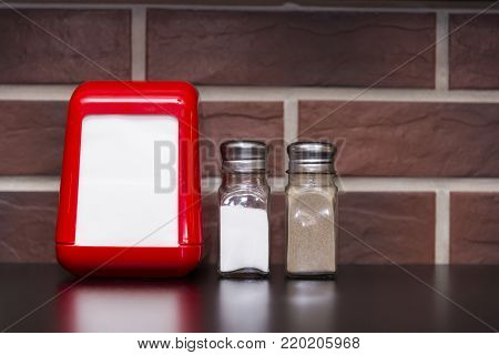 On the table in the cafe are a red napkin stand, salt shaker and pepper shaker