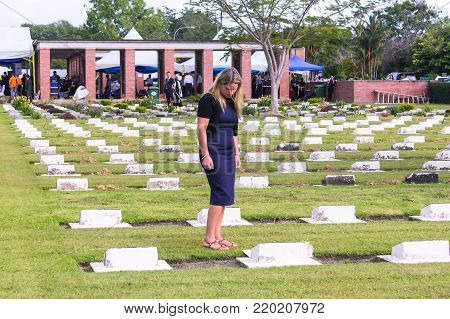 Labuan,Malaysia-Nov 12,2017:Young woman in mourning clothes standing above headstone at Commonwealth World War II graveyard in Labuan,Malaysia.