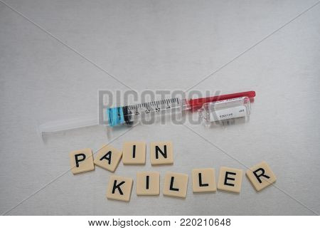 Pain Killer spelled with tile letters placed in a haphazard fashion with an syringe filled with clear liquid and an empty glass Fentanyl vial on its side. Photographed from above on a stainless steel background. Image has copy space.