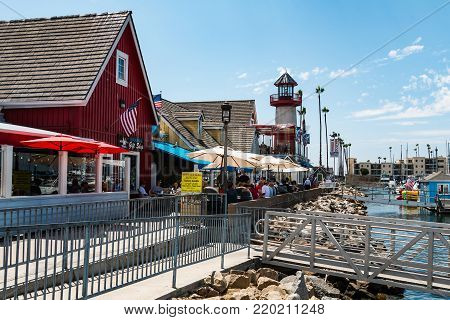 OCEANSIDE, CALIFORNIA - SEPTEMBER 9, 2017:  People in restaurants at Oceanside Harbor Village, a popular tourist attraction for sportfishing, shopping and waterfront dining in San Diego County.