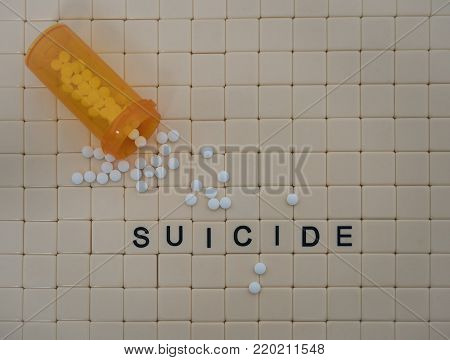 Tan tiles with black capital letters spelling suicide set in a background of small tan tiles. An open orange prescription bottle with white oxycodone tablets spilling forth is in the upper right corner. Photographed from above. poster