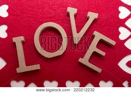 the word love made with wooden letters on red background