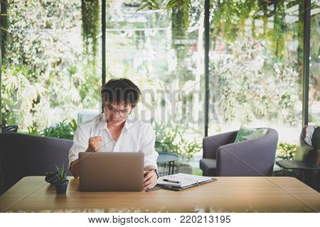 young start up man raise fist with yes gesture at office. freelance male entrepreneur glad with successful project. businessman working at workplace. success, business, entrepreneur concept.