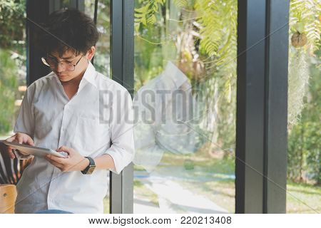 Businessman Using Tablet Computer At Workplace. Startup Man Working With Touchpad At Office.  Young
