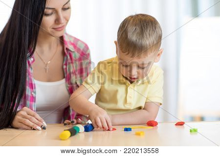 child kid boy and mom playing colorful clay toy at nursery or kindergarten