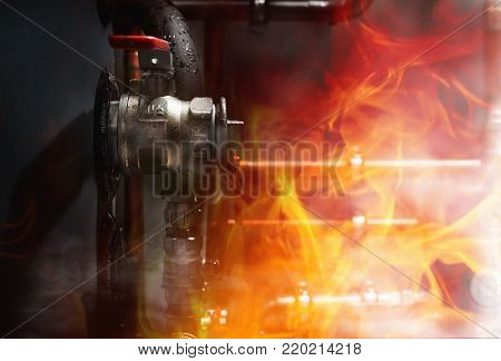 Fire, smoke and steam in a boiler room. Copper pipes  and valves on a wet boiler. Close up.Phrase on boiler