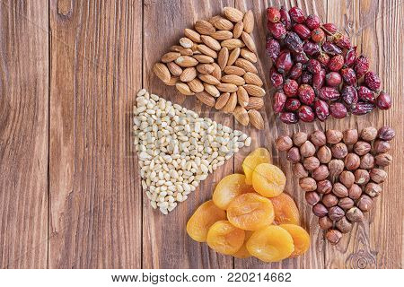Dried apricots and nuts on a wooden table, round composition. Circle divided into parts made of a nuts and dried apricots. Concept of healthy snack. Various nuts and dried fruits with copy space.