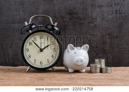 Retro alarm clock with white piggy bank and stack of coins on wooden table and black background as long term savining money or retirement investment concept.