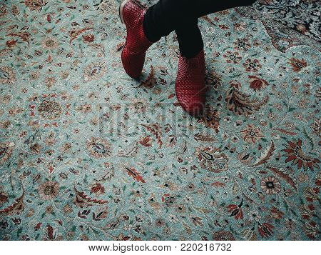 Woman standing on a colorful oriental pattern carpet with fashion red shoes in a waiting pose