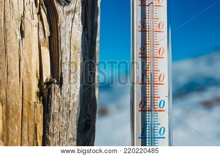 Thermometer strapped on a post outside in the mountain, shallow depth of field