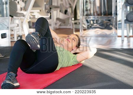 Fitness woman lying doing crunches at gym. Sporty young attractive woman practicing abdominal, crunches, sit ups, rock press exercise, working out. Healthy lifestyle, gymnastics, weightloss concept