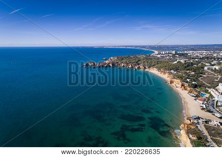 Aerial view of the coastline with beautiful beaches between Portimao and Lagos in Algarve, Portugal; Concept for travel in Portugal and summer vacations in Algarve