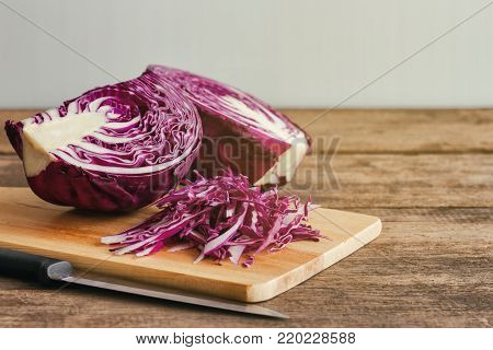 Chopped or sliced fresh purple cabbage on cutting board to shredded with knife kitchen. Shredded purple cabbage on wood table with copy space. Prepare vegetable for cooking cabbage salad or coleslaw. Homemade food concept. Sliced cabbage ready to cook.