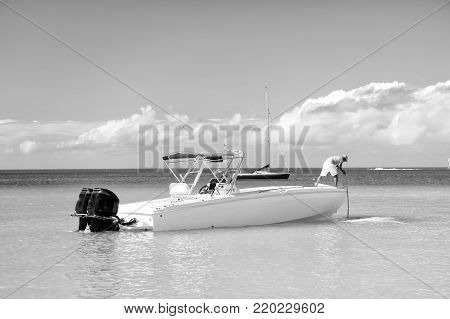 man, yachtsman on motorboat, yacht on sea, ocean water, coast sunny summer outdoor on blue cloudy sky background in St. John, Antigua, traveling and vacation, sport and sailing