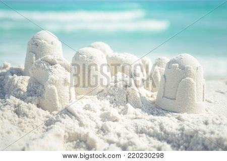 Sandcastle on Florida beach with white sand, blurred ocean on background