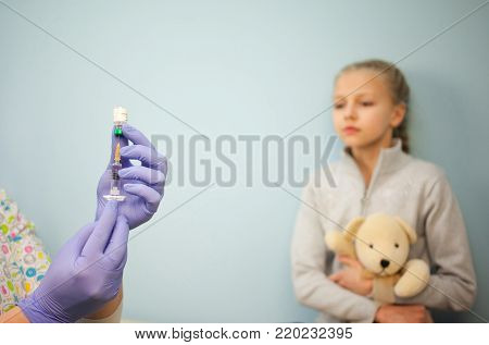 The pediatrician or nurse in a syringe vaccine, a girl in the background with the toy, the child vaccination