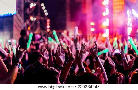 Crowd clap or hands up at concert stage lights and people fan audience raising hands silhouette with spotlights glowing effect in the music festival rear view