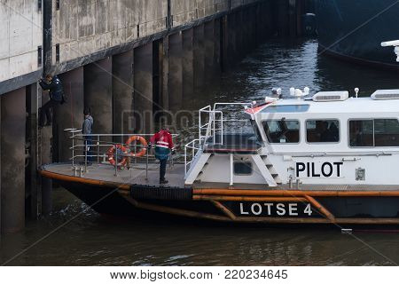HAMBURG, GERMANY - DECEMBER 20, 2016: Pilot boat picking up a pilot from a high Elbe river quay