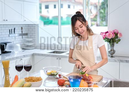 Cooking asian woman housewife in the kitchen making healthy food with vegetables diet dinner at home
