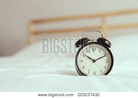 Sleeping,Wake up in the morning concept.Black alarm clock on bed in room for waking up and ringing bell