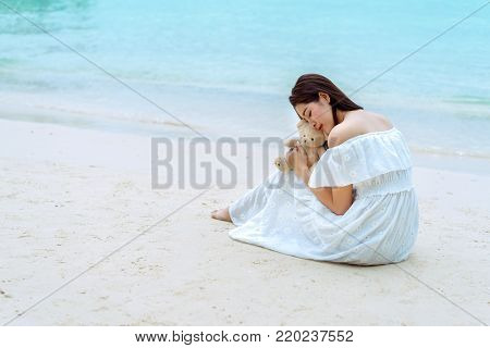 Asian single woman sitting with teddy bear at seaside beach friendship lonely everywhere on tropical sea and wearing white dress