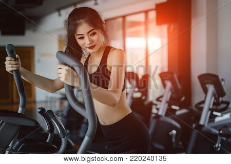 Asian woman Exercise Elliptical cardio running workout at fitness gym taking weight loss with machine aerobic for slim and firm healthy lifestyle in the morning.