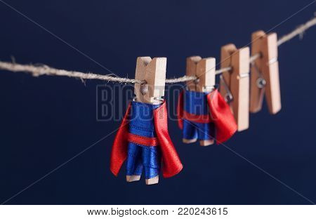 Super team concept photo with clothespin superheroes in blue suit and red cape. Big small powerful heroes. Dark background. soft focus. macro view, shallow depth of field.