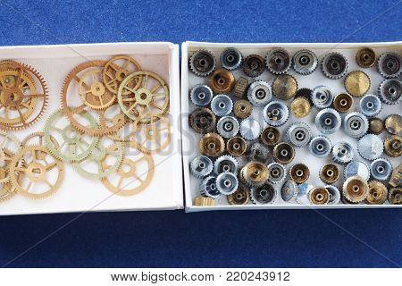 Opened paper boxes with aged grunge cogs wheels gears collection set. macro view, blue background. Shallow depth of field, soft focus. up view.