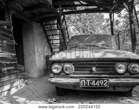 DEBNEVO, BULGARIA - SEPTEMBER 25, 2011: Old abandoned Moskvitch in a mean rural cattle-shed at the Forebalkan village of Debnevo, Bulgaria