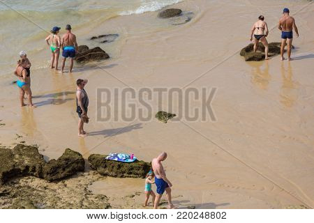 ALBUFEIRA, PORTUGAL - AUGUST 24, 2017: People at the famous beach of Olhos de Agua in Albufeira. This beach is a part of famous tourist region of Algarve.