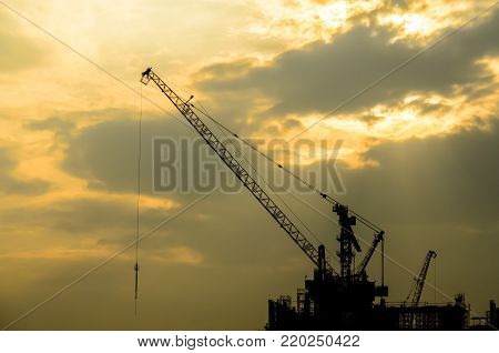 The Crane Truck has under construction under the lighting sky in the evening.