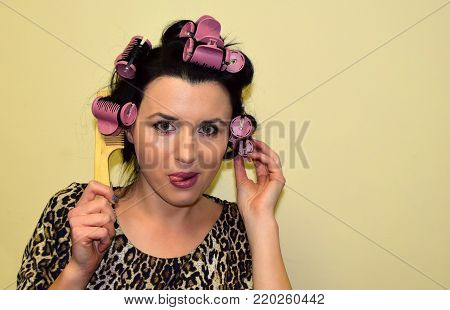 The young woman has the locks of hair which are reeled up on hair curlers. The woman uses hair curlers of hair for creation of a beautiful hairstyle.The woman holds a hairbrush in hand. She puts out the tongue.