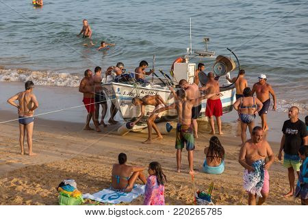 ALBUFEIRA, PORTUGAL - AUGUST 24, 2017: The last fishing ship of Olhos de Agua in Albufeira. The Tourists help the fisherman taking the boat in to the water