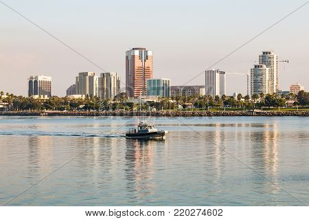 LONG BEACH, CALIFORNIA - SEPTEMBER 8, 2017:  Long Beach Harbor Police patrol through the bay in the early morning, in front of a downtown cityscape.