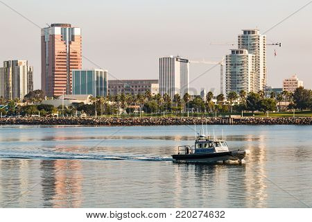 LONG BEACH, CALIFORNIA - SEPTEMBER 8, 2017:  A Long Beach Harbor Police boat patrols the bay at dawn. with downtown skyscrapers in the background.